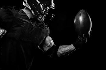 Fototapeta Sport concept. American football sportsman player on black background. Sport concept.