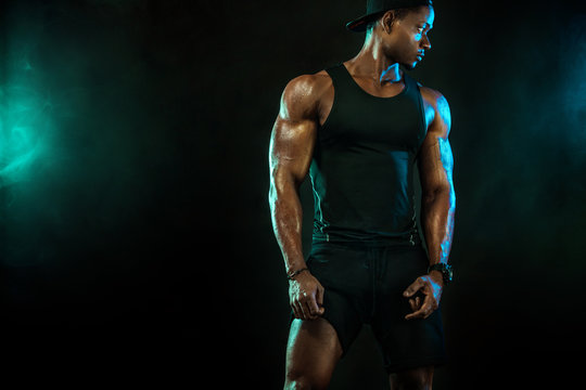 Sports men athlete on dark background. Power athletic guy bodybuilder doing fitness training.
