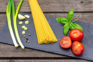 raw spaghetti decorated with spring onions, basil, tomatoes and garlic.