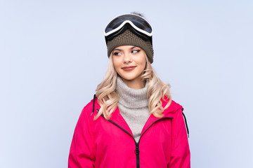 Skier teenager girl with snowboarding glasses over isolated blue background standing and looking to...