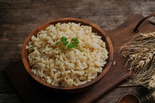 Bowl of cooked Whole grain brown rice  on wooden background overhead view