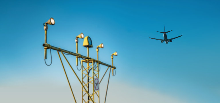 Drone zone sign on approach lighting system at runway. Airport airspace prohibition drones fly sign. Flying plane in background.