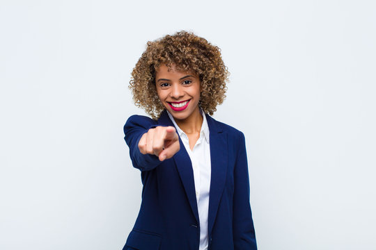 young woman african american pointing at camera with a satisfied, confident, friendly smile, choosing you against flat wall