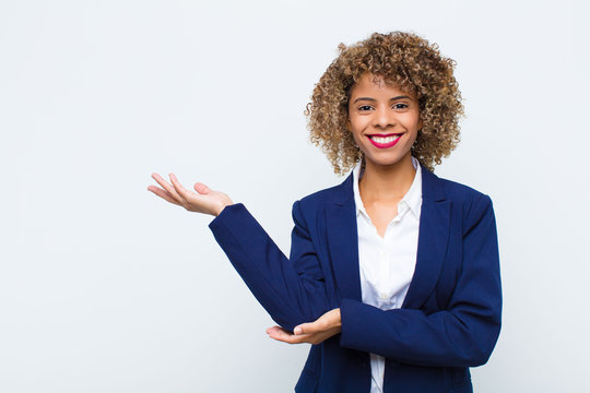 young woman african american smiling proudly and confidently, feeling happy and satisfied and showing a concept on copy space against flat wall