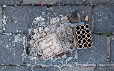 Altenburg / Germany - January 2020: Ashes and paper remains of a fireworks battery on the pavement of the central market square on New Year's afternoon