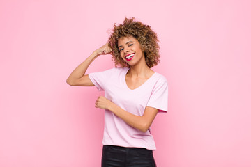 young african american woman feeling happy, satisfied and powerful, flexing fit and muscular biceps, looking strong after the gym against pink wall