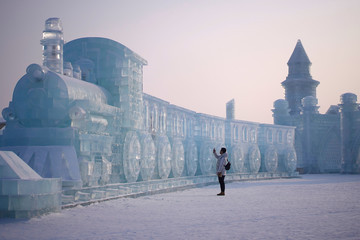 A man visits ice sculptures ahead of the annual Harbin International Ice and Snow Sculpture Festival in the northern city of Harbin