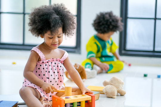 Portrait of one young African mixed race girl is playing with toys in front of the other african boy and look like she enjoy and happy with this activity.