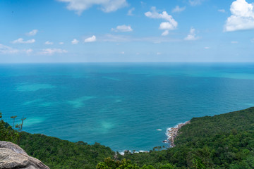Wall Mural - Beautiful stunning vibrant landscape, blue sea and sky with white clouds, aerial view of the sea and green jungle