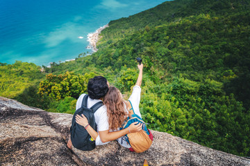 Wall Mural - Happy beautiful young couple of travelers man and woman on top of a mountain with ocean view. Romantic travels, honeymoon