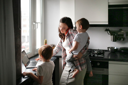 Busy mom with two children works on laptop kitchen