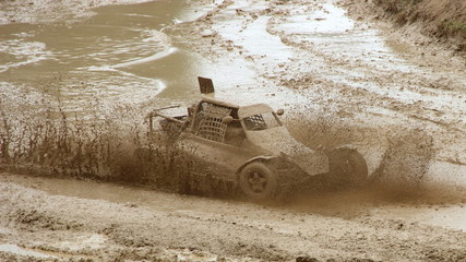 Speed racing Buggy car in muddy puddle dirt splash on atv off road track, front side view