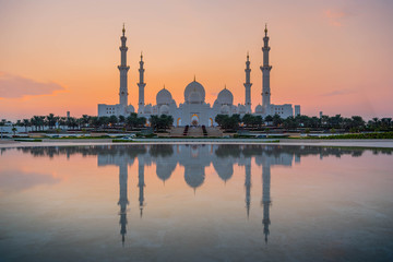 bu Dhabi, UAE, United Arab Emirates: Stunning view of Abu Dhabi Sheikh Zayed Mosque (also known as Grand Mosque) at dusk, reflection in water, illuminated at sunset, golden blue hour