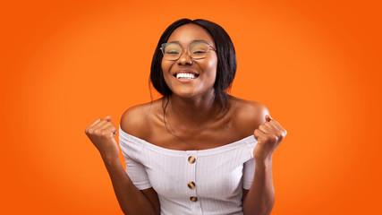 Joyful Girl Celebrating Success Shaking Fists Over Orange Background, Studio