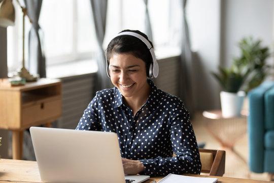 Happy indian young girl wear headphones watching listening online course