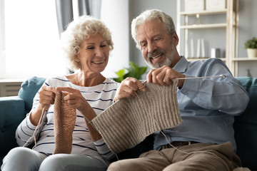 Happy 60s spouses knitting seated on couch enjoy common activity