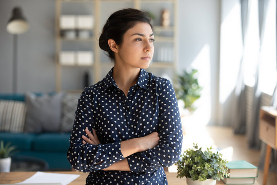 Serious confident indian woman looking away dreaming of success
