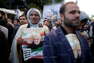 A man holds a picture of Soleimani and al-Muhandis during their funeral procession in Ahvaz