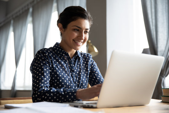 Smiling indian girl student professional typing on laptop at table