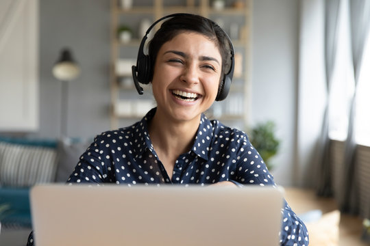 Cheerful indian woman wear wireless headset laughing with laptop