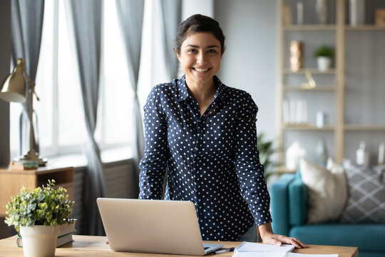 Happy indian girl looking at camera at home with laptop
