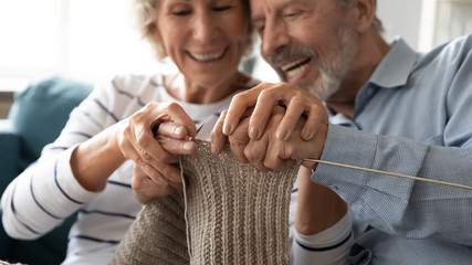 Close up image elderly wife teaches husband how to knit