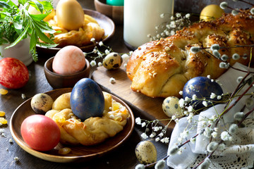 Easter table. Easter pastries and colored eggs on a wooden countertop.