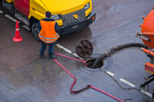 Repair work on troubleshooting or communal service work. Open iron hatch with cable going inside.  Repair on networks of water supply, heating. The hatch is open. The pipe repair. Special machinery.