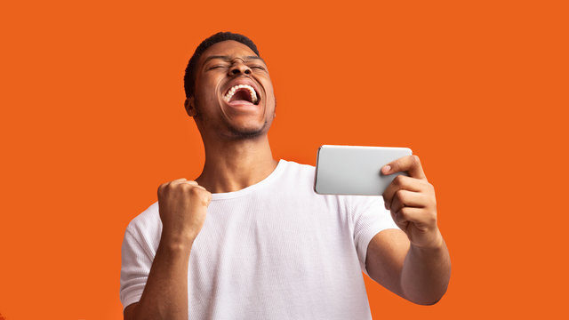 Excited afro guy holding phone celebrating success