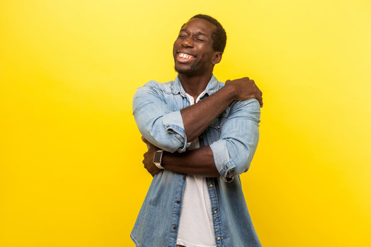 I love myself. Portrait of self-satisfied happy man in denim casual shirt cuddling himself and smiling with pleased delighted expression, egoist. indoor studio shot isolated on yellow background