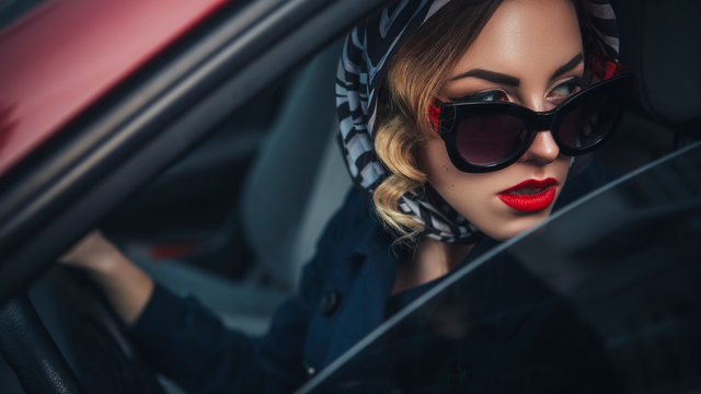 Beautiful brunette sexy spy agent (killer or police) woman in leather jacket and jeans with a gun in her hand driving a car after someone, to catch him