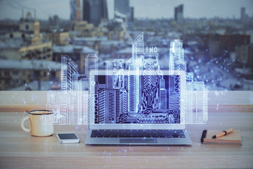 Desktop computer background in office and big town buildings hologram drawing. Double exposure....