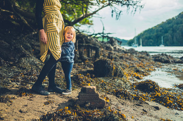 Toddler grabbing his mother's dress by the river in autumn