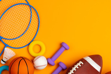 Assortment of sport equipment on yellow background, top view