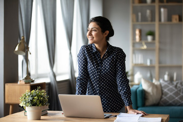 Dreamy indian woman looking away dreaming at home with laptop