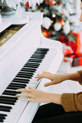Beautiful brunette girl plays on a white piano on a background of the Christmas tree. Music. Melody