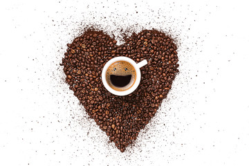 Photo sur Toile Cafe heart made from coffee beans and ground coffee on a white background. in the center is a cup, in a cup from coffee foam a happy smiling face. invigorating drink concept