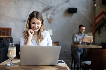 Portrait of a young beautiful businesswomen enjoying coffee during work on laptop computer,
