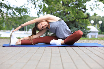 Attractive young fitness woman exercising outdoors, stretching exercises.