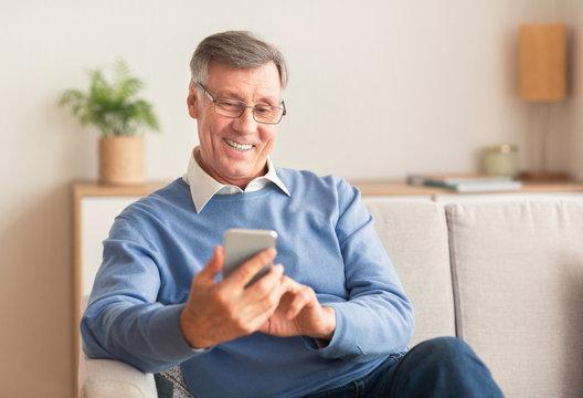 Joyful Elderly Man Using Cellphone Sitting On Sofa At Home