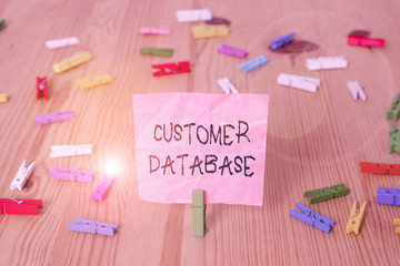 Conceptual hand writing showing Customer Database. Concept meaning uptodate on customer information records and data Colored crumpled papers wooden floor background clothespin Wall mural