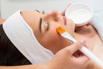Fototapeta Kobieta w spa. Pielęgnacja cery, nakładanie maski w salonie kosmetycznym.  obraz