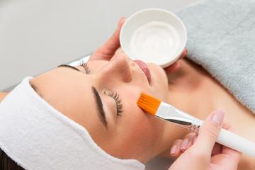 Zbliżenie na twarz kobiety podczas zabiegu kosmetycznego. Kosmetyczka nakłada maskę pędzlem na twarz kobiety. Pielęgnacja cery.