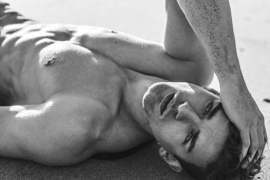 Sexy portrait of topless male model lying on the beach. Black and White.