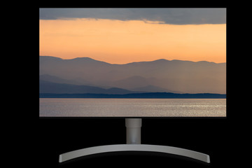 UHD monitor with sea and mountains image on it