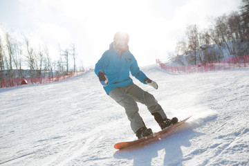 Man snowboarder snowboarding on fresh white snow on ski slope on Sunny winter day Snowboarder balances when lands after fly on snowboard over snowy hillside
