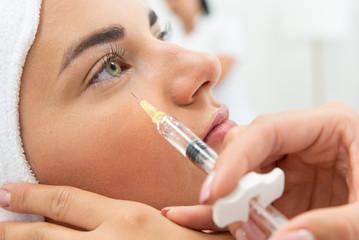 Fototapeta Kosmetolog wykonuje zabieg przeciwzmarszczkowy. Ostrzykiwanie toksyną botulinową, redukcja zmarszczek. Botoks w klinice medycyny estetycznej. Wstrzykiwanie wypełniacza pod oczy.  obraz