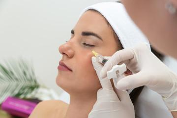 Obraz Kosmetolog wykonuje zabieg przeciwzmarszczkowy. Ostrzykiwanie kwasem, redukcja zmarszczek. Botoks w klinice medycyny estetycznej. Wstrzykiwanie wypełniacza.  - fototapety do salonu