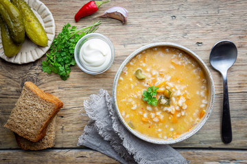 Soup with pickled cucumbers and pearl barley - rassolnik on wooden background, top view