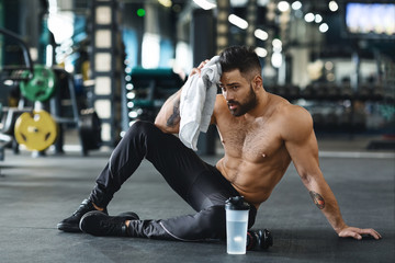 Handsome athlete wiping sweat after workout at gym